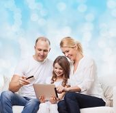 family, christmas holidays, shopping, technology and people - smiling family  with tablet pc computer and credit card over blue lights background