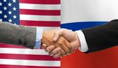 partnership, politics, gesture and people concept - close up of handshake over american and russian national flags background