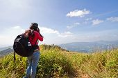 Hiking Tourist Taking Photos Of The Alpine Landscape