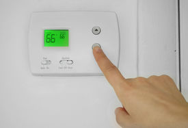 foto of temperature  - A woman adjusting a wall thermostat temperature - JPG