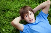 stock photo of schoolboys  - Happy teenager lying on grass in park outdoor schoolboy - JPG