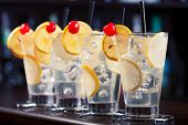 foto of collins  - Four Tom Collins cocktails shot on a bar counter in a night club - JPG