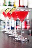 stock photo of cosmopolitan  - Four Cosmopolitan cocktails shot on a bar counter - JPG