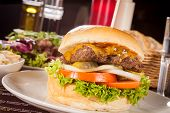 picture of bread rolls  - Tasty traditional cheeseburger with a ground beef patty topped with melted cheese and served with onion rings tomato and curly leaf lettuce on a round white bread roll close up view - JPG