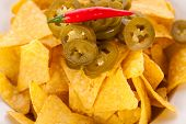 foto of nachos  - Bowl of crisp golden corn nachos with cheese sauce or dip and olives served as a starter or appetizer to a meal