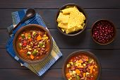 image of kidney beans  - Overhead shot of two rustic bowls of vegetarian chili dish made with kidney bean carrot zucchini bell pepper sweet corn tomato onion garlic with tortilla chips and raw kidney beans on the side photographed on dark wood with natural light - JPG