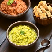 foto of kidney beans  - Rustic bowl of homemade zucchini and parsley spread garnished with fresh parsley leaf red kidney bean spread and sticks of wholegrain bread in the back photographed on dark wood with natural light  - JPG