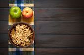 pic of crisps  - Overhead shot of a rustic bowl of baked apple crumble or crisp with fresh apples on a kitchen towel photographed on dark wood with natural light - JPG