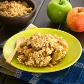 picture of crisps  - Freshly baked apple crumble or crisp served on plate with wooden spoon fresh apples and a rustic bowl of apple crumble in the back photographed on dark wood with natural light  - JPG