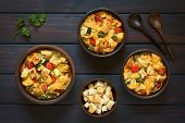 stock photo of dark side  - Overhead shot of savory baked vegetarian bread pudding made of zucchini bell pepper tomato and diced baguette seasoned with thyme and parsley in rustic bowls ingredients and wooden spoons on the side photographed on dark wood with natural light - JPG