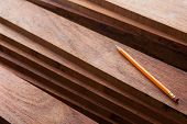 picture of carpentry  - Hard wood lumber stacked with pencil on top - JPG