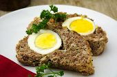 stock photo of meatloaf  - easter meal meatloaf bread with boiled eggs on a plate rustic wooden background - JPG