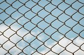 stock photo of chain link fence  - chain link fence blue sky clouds background - JPG