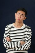 foto of turn-up  - Frustrated young Asian man with crossed hands rolling eyes up - JPG