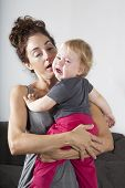 foto of cry  - portrait of one year age blonde lovely cute caucasian white baby grey shirt pink trousers looking at camera face indoors crying and scream shout with tears eyes in brunette woman mother arms embrace hug - JPG
