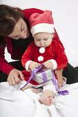 stock photo of santa baby  - one year age caucasian blonde baby Santa Claus disguise with brunette woman mother red cardigan green trousers opening silver wrapped paper box gift Christmas on white background - JPG