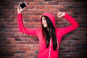 stock photo of rap-girl  - Happy woman listening music and dancing in headphones over brick wall - JPG