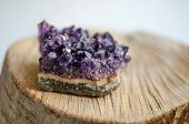 pic of violets  - Raw violet amethyst rock with reflection on natural wood macro - JPG