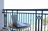 stock photo of lax  - computer laptop on balcony with sea view and coffee - JPG