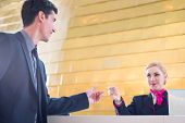 stock photo of check  - Hotel receptionist check in man giving key card - JPG