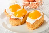 stock photo of yolk  - Fried eggs cookies with peach yolks on a white plate - JPG