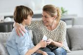 picture of adolescent  - Mother giving money to adolescent for reward - JPG