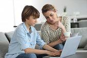 foto of homework  - Mother looking after son doing homework on laptop - JPG