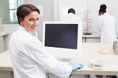pic of scientist  - Smiling scientist using computer while colleagues working in the laboratory - JPG