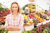 picture of farmers market vegetables  - Female Stall Holder At Farmers Fresh Food Market - JPG