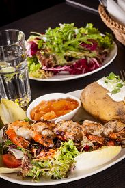 image of endive  - Grilled prawns with a green leafy lettuce and endive salad and a jacket potato topped with sour cream served on a white plate close up high angle view on white - JPG