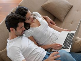 pic of life-support  - happy young relaxed  couple working on laptop computer at modern home indoor - JPG