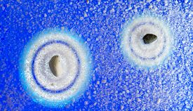 foto of sand lilies  - Top view of the original Zen garden stone two stone circles in the sand blue tone - JPG