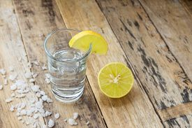 picture of vodka  - Vodka with lemon on wooden table background  - JPG