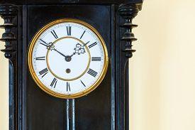 picture of pendulum  - Closeup old big wooden pendulum clock hanging on wall - JPG