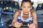 Endurance training fitness woman doing cardio workout. Exercise on gym bike bicycle. poster