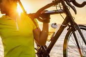 Cyclist carrying road bike at sunset after long day of biking activity riding outdoors. Healthy man  poster