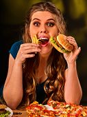 Woman eating french fries and hamburger with pizza. Portrait of student consume fast food on table.  poster