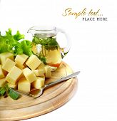 Cheese on a wooden plate and a pitcher of olive oil and herbs. Shallow DOF