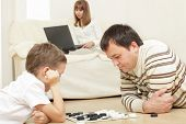picture of draught-board  - Father with the son playing draughts at home - JPG