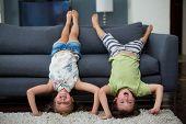 Playful siblings having fun in living room at home poster