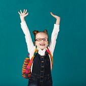 Funny Smiling Little Girl With Big Backpack Jumping And Having Fun Against Blue Wall. Looking At Cam poster