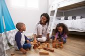 Mother And Children Playing With Building Blocks In Bedroom poster