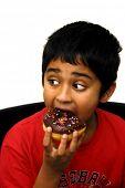 An handsome indian boy eating a chocolate dounut