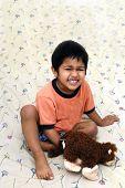 Um garoto bonito, jogando com um brinquedo de pelúcia