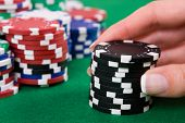 Female hand putting black poker chips into game.