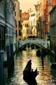 Gondola silhouette on venetian canal at evening.