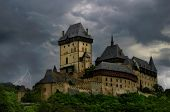 Famous ancient Karlstejn Castle under the stormy clouds in Karlstejn, Czech Republic.