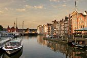 View on canal (Amstel river) and old houses in Amsterdam, Netherlands.