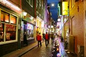 Bars and coffee shops on the street full of tourists at night in famous Red Light District in Amster