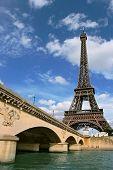 Vertical oriented photo of Eiffel Tower and fragment of bridge over the Seine River in Paris, France